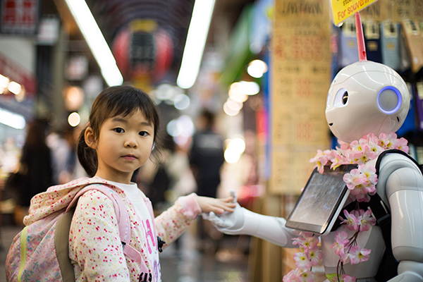 A little girl making friends with a robot at Kuromon Market in Osaka Photo by Andy Kelly on Unsplash