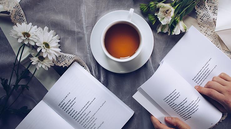 tazza di caffè con libri e fiori Photo by Thought Catalog on Unsplash